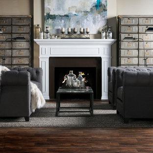 Immagine di un soggiorno industriale di medie dimensioni e chiuso con pareti beige, pavimento in legno massello medio, camino classico, cornice del camino in legno e nessuna TV