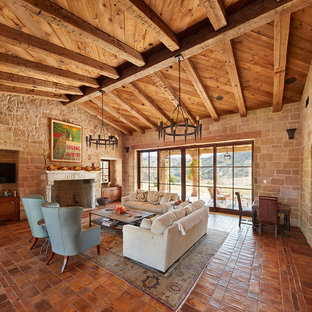 This is an example of a mid-sized country open concept living room in Orange County with terra-cotta floors, a standard fireplace, a stone fireplace surround and orange floor.