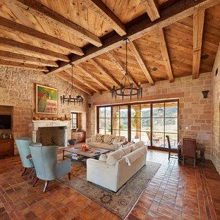 オレンジカウンティの中くらいのラスティックスタイルのおしゃれなLDK (テラコッタタイルの床、標準型暖炉、石材の暖炉まわり、オレンジの床) の写真