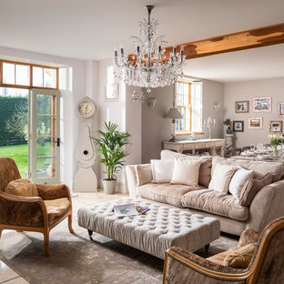 This is an example of a large country open plan living room in Cornwall with white walls and beige floors.