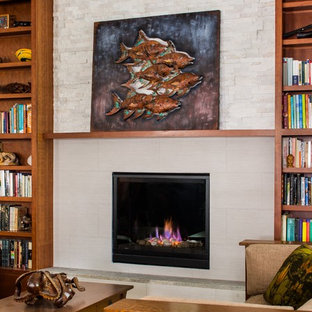 Arts and crafts open concept living room in Atlanta with light hardwood floors, a standard fireplace and a tile fireplace surround.