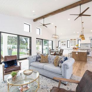 Großes, Repräsentatives, Offenes Landhausstil Wohnzimmer mit weißer Wandfarbe, braunem Holzboden, Kamin, Wand-TV, Kaminsims aus Holz und braunem Boden in Orange County