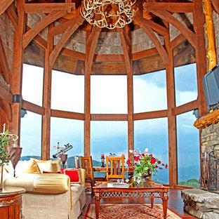 Diseño de salón para visitas abierto, rural, grande, con paredes marrones, suelo de madera en tonos medios, chimenea tradicional, marco de chimenea de piedra y televisor colgado en la pared