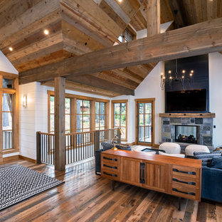 Example of a mid-sized mountain style open concept medium tone wood floor and brown floor living room design in Other with white walls, a two-sided fireplace, a stone fireplace and a wall-mounted tv