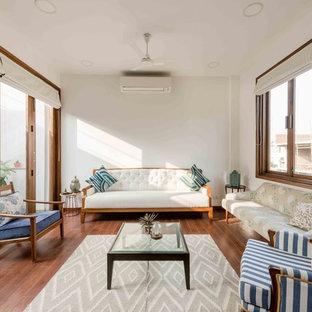 Réalisation d'un salon asiatique de taille moyenne et fermé avec un mur blanc, un sol en bois brun et un sol marron.