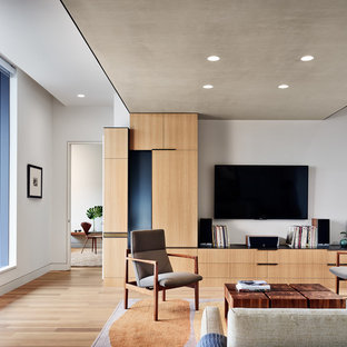 Trendy formal and open concept light wood floor and beige floor living room photo in Austin with gray walls and a wall-mounted tv