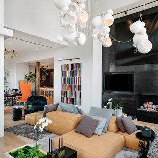 Idee per un ampio soggiorno minimal con parquet chiaro, camino ad angolo, cornice del camino in metallo e parete attrezzata