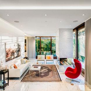 Esempio di un soggiorno minimal di medie dimensioni e aperto con sala formale, pavimento in marmo, camino bifacciale, nessuna TV, pavimento grigio, pareti bianche e cornice del camino in pietra