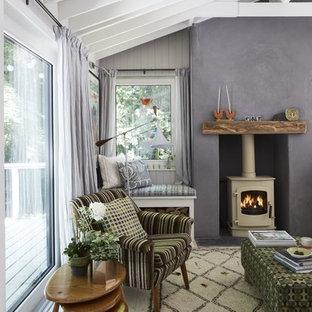 Diseño de salón rural, pequeño, con paredes grises, suelo de madera clara y estufa de leña