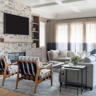 Exemple d'un salon bord de mer de taille moyenne et ouvert avec un mur beige, un sol en bois clair, une cheminée standard, un manteau de cheminée en pierre, un téléviseur fixé au mur, un sol beige et un plafond à caissons.