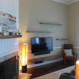 Imagen de biblioteca en casa tradicional renovada, pequeña, con paredes marrones, suelo de madera oscura, chimenea de esquina, marco de chimenea de madera, televisor colgado en la pared y suelo marrón