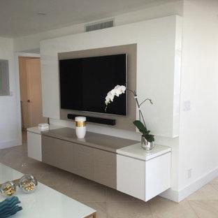 Imagen de salón abierto, minimalista, grande, sin chimenea, con paredes blancas, televisor colgado en la pared y suelo beige