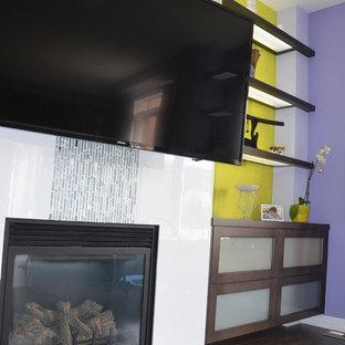Immagine di un soggiorno moderno di medie dimensioni e aperto con pareti gialle, parquet scuro, camino classico, cornice del camino piastrellata e parete attrezzata