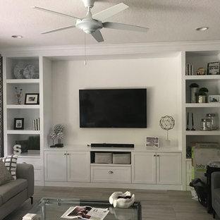 Ispirazione per un grande soggiorno minimal chiuso con pareti grigie, pavimento in legno massello medio, nessun camino, TV a parete e pavimento grigio