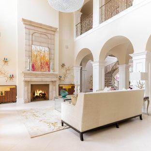ダラスの巨大な地中海スタイルのおしゃれな独立型リビング (フォーマル、ベージュの壁、ライムストーンの床、標準型暖炉、石材の暖炉まわり、テレビなし、白い床) の写真