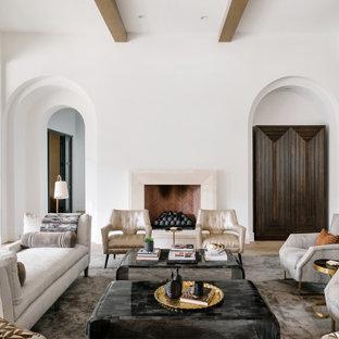 Réalisation d'un très grand salon méditerranéen avec une salle de réception, un mur blanc, un sol en bois clair, une cheminée standard et un sol beige.