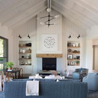 サンフランシスコのカントリー風おしゃれなLDK (白い壁、濃色無垢フローリング、標準型暖炉、茶色い床、三角天井、塗装板張りの壁) の写真