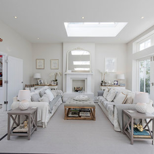 Photo of a nautical formal enclosed living room in London with white walls, a standard fireplace and white floors.