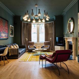 ロンドンの広いコンテンポラリースタイルのおしゃれなリビング (ミュージックルーム、標準型暖炉、石材の暖炉まわり、コーナー型テレビ、緑の壁、無垢フローリング、茶色い床) の写真