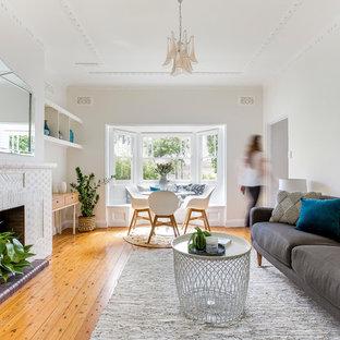 Ispirazione per un soggiorno nordico di medie dimensioni con pareti bianche, parquet chiaro, camino bifacciale, cornice del camino in mattoni e pavimento beige