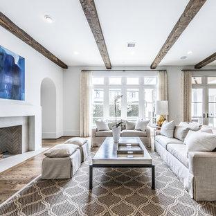 Foto de salón mediterráneo, grande, sin televisor, con paredes blancas, suelo de madera oscura, chimenea tradicional, marco de chimenea de yeso y suelo blanco