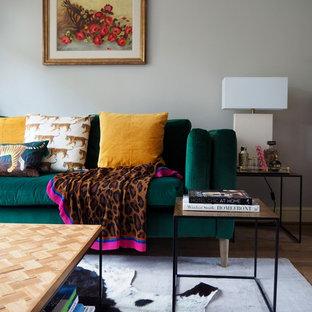 Foto di un soggiorno eclettico di medie dimensioni e chiuso con sala formale, pareti grigie, pavimento in laminato, camino classico, cornice del camino in cemento, TV autoportante e pavimento marrone