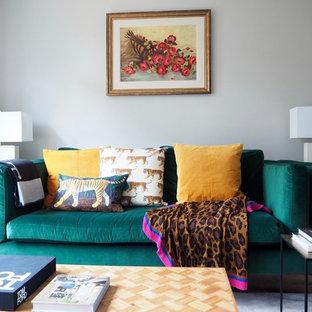 サリーの中サイズのエクレクティックスタイルのおしゃれな独立型リビング (フォーマル、グレーの壁、ラミネートの床、標準型暖炉、コンクリートの暖炉まわり、据え置き型テレビ、茶色い床) の写真