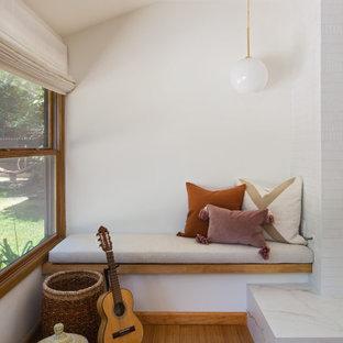 Foto på ett mellanstort skandinaviskt allrum med öppen planlösning, med ett finrum, vita väggar, bambugolv, en standard öppen spis, en spiselkrans i trä och gult golv