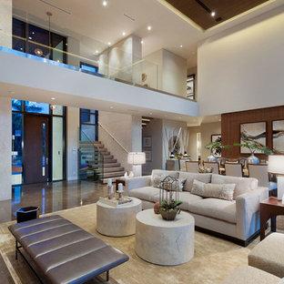 Cette image montre un grand salon minimaliste ouvert avec un mur beige, un sol en marbre, une cheminée ribbon, un manteau de cheminée en pierre et aucun téléviseur.