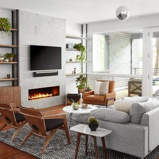 На фото: открытая гостиная комната среднего размера в современном стиле с музыкальной комнатой, серыми стенами, паркетным полом среднего тона, горизонтальным камином, телевизором на стене и коричневым полом с