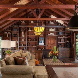 Réalisation d'un grand salon avec une bibliothèque ou un coin lecture chalet fermé avec un sol en bois foncé, une cheminée standard et un manteau de cheminée en pierre.