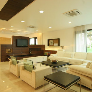 This is an example of a modern formal living room in Atlanta with beige walls, marble floors and a wall-mounted tv.