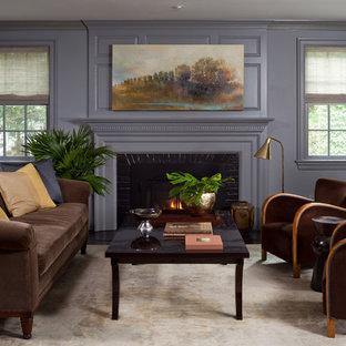 Esempio di un soggiorno classico con libreria, pareti viola, camino classico e cornice del camino in mattoni