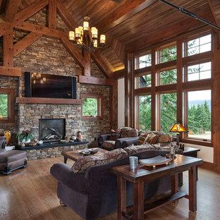 シアトルの中サイズのラスティックスタイルのおしゃれなLDK (ベージュの壁、無垢フローリング、標準型暖炉、石材の暖炉まわり、壁掛け型テレビ、茶色い床) の写真