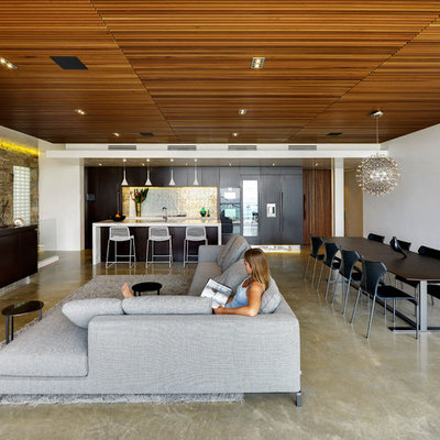Inspiration for a mid-sized contemporary open concept concrete floor and gray floor living room remodel in Gold Coast - Tweed with white walls and no fireplace