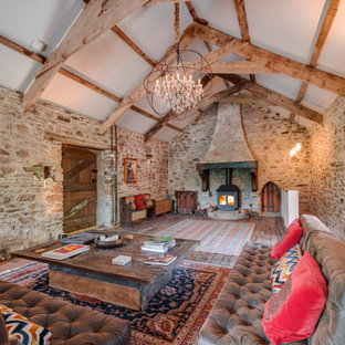 Design ideas for a large rural open plan living room in Devon with brown walls, dark hardwood flooring, a wood burning stove, brown floors, exposed beams and a vaulted ceiling.