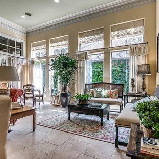 オクラホマシティの広いトラディショナルスタイルのおしゃれなLDK (フォーマル、黄色い壁、ライムストーンの床、標準型暖炉、石材の暖炉まわり、埋込式メディアウォール、白い床) の写真
