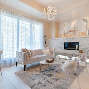 バンクーバーの大きいコンテンポラリースタイルのおしゃれな独立型リビング (白い壁、淡色無垢フローリング、標準型暖炉、石材の暖炉まわり、ベージュの床) の写真