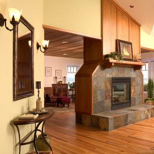 シアトルの中サイズのビーチスタイルのおしゃれなLDK (緑の壁、無垢フローリング、両方向型暖炉、木材の暖炉まわり) の写真