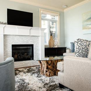 バンクーバーの中サイズのビーチスタイルのおしゃれなLDK (タイルの暖炉まわり、青い壁、標準型暖炉、据え置き型テレビ) の写真