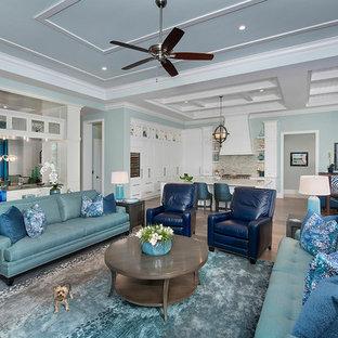 Ejemplo de salón abierto, costero, sin chimenea, con paredes verdes y suelo de madera clara