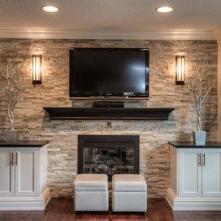 Esempio di un grande soggiorno stile americano aperto con pavimento in legno massello medio, camino classico, cornice del camino in pietra e parete attrezzata