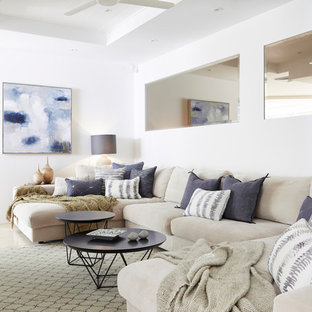 Beach style living room in Other with white walls and beige floor.
