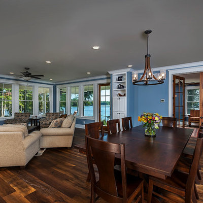 Example of a mid-sized farmhouse open concept medium tone wood floor and brown floor living room design in Other with blue walls, a standard fireplace, a stone fireplace and a wall-mounted tv