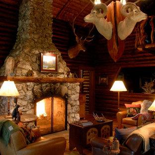 Modelo de salón cerrado, rústico, pequeño, con paredes marrones, chimenea tradicional y marco de chimenea de piedra