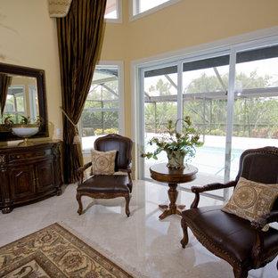 Immagine di un soggiorno tropicale aperto con pareti gialle, pavimento in marmo, camino classico, cornice del camino in intonaco e pavimento beige