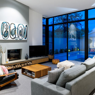This is an example of a contemporary living room in Adelaide with white walls, carpet, a standard fireplace and grey floor.