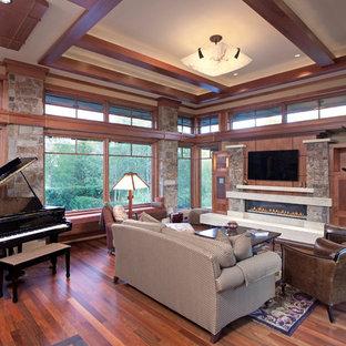 Ispirazione per un soggiorno american style aperto con sala della musica, pareti beige, pavimento in legno massello medio, camino lineare Ribbon, cornice del camino in pietra e TV a parete