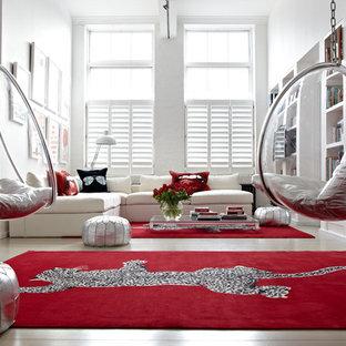Inspiration pour un salon avec une bibliothèque ou un coin lecture design avec un mur blanc, un sol en bois clair et aucune cheminée.