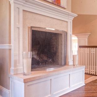 Idée de décoration pour un salon tradition avec un mur beige, un sol en bois brun, une cheminée standard et un manteau de cheminée en carrelage.